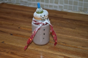 Snowman hotchocolate in a baby food jar with material for a scarf, doughnut with icing pen eyes and mouth for a face, half a grape for a hat, a straw to hold everything together and a sprinkling of icing sugar for snow!