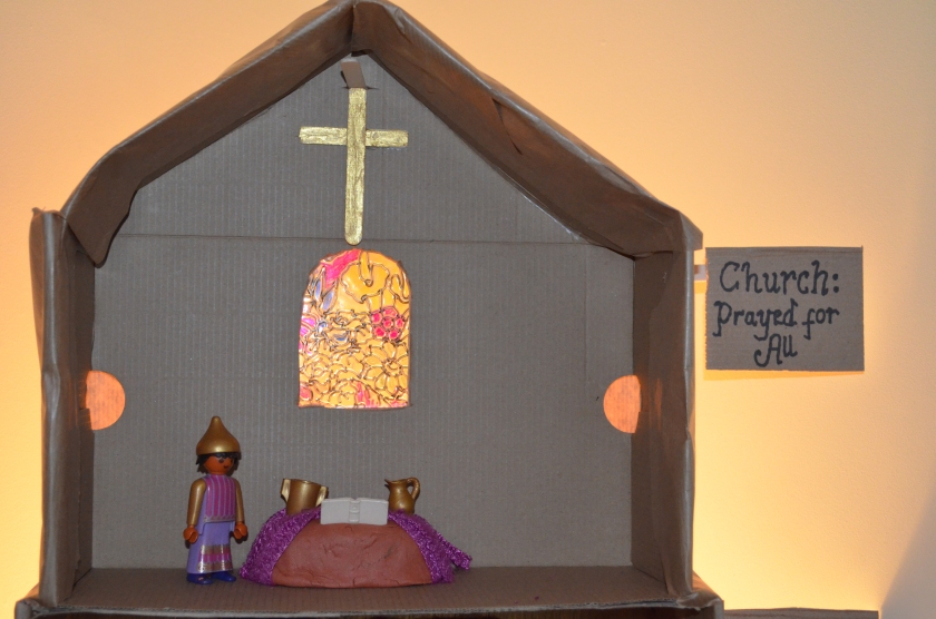 The church who prayed for all...I used one of our stain glass windows the children had made in a previous study, placing it behind a hole in the wall.  We painted a wooden cross gold and hung it above.  The alter is made of clay and is covered in purple cloth, with a playmobil bible, golden jug and chalise.  We popped in a playmobil pope!