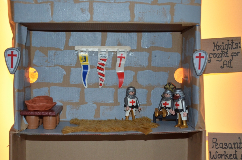 The knights who fought for all....We made a castle and used a washing up sponge to sponge tiles onto the box.  We hung playmobil flags from the wall and shields from the exterior.  On the table was a clay bowl with food and other bits and pieces