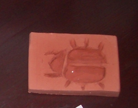 C's sunken relief in the form of a scarab beetle. We used a stencil as a guide