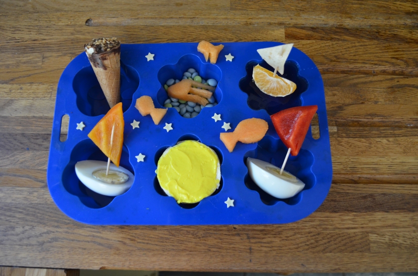 Lower row: half egg boats with pepper sails and tortilla and soft cheese yellow ball Upper row: mini ice cream cone, mini blue choc chip sea bed with a melon jelly fish and blue jelly and an orange boat with tortilla sail.  Muffin decorated with tiny star fish and cut out melon fish.