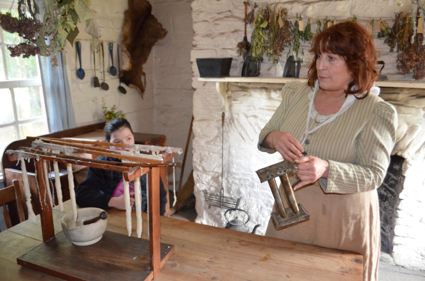The re-enactor demonstrating how to dip candles
