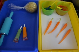 Cookie dough and icing pens for carrot cookie decorating and carrots, paint and paper for carrot printing