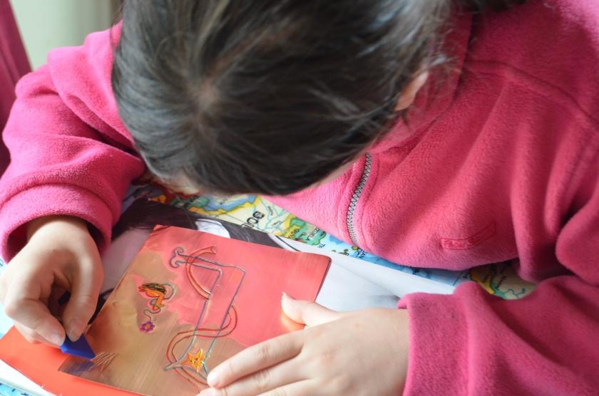 L10 scraping her design using a plastic shape
