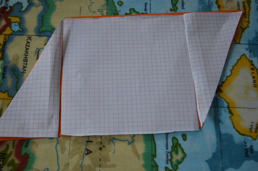The orange parallogram is under the cut out squared paper one.  It can be seen that they cover exactly the same area