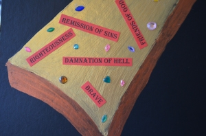 A close up of the bottom of the cross, showing the words and the jewels