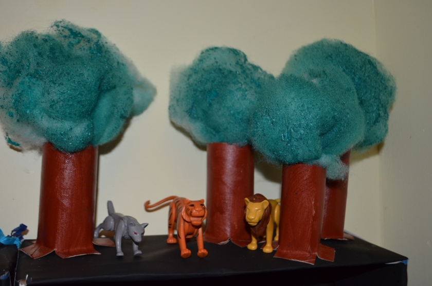 We made the trees from polyester filling which we sprayed with watered down acrylic paint and painted toilet rolls.  The beasts were playmobil figures we already owned.