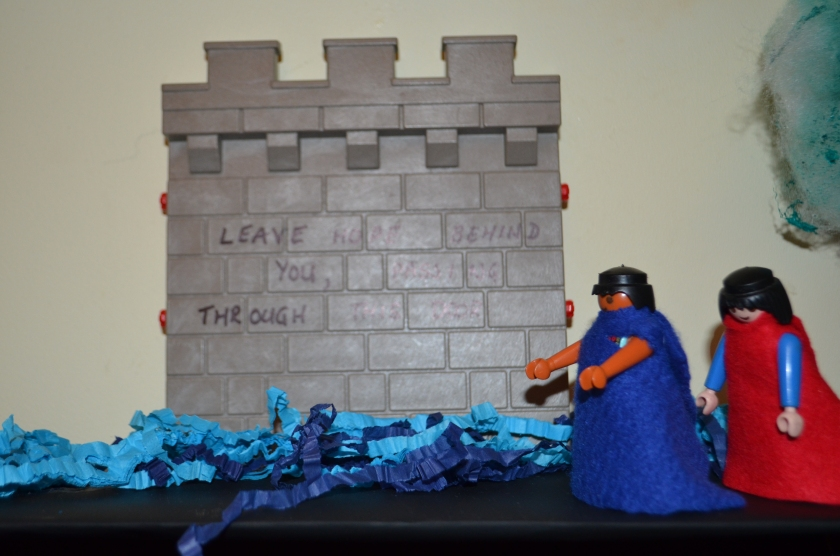 We covered two Play mobil figures in red and blue felt to represent Dante and Virgil, I used crepe paper for the river and a playmobil castle door for the Gate of Hell.  We wrote on the gate the words as they were written in our translation